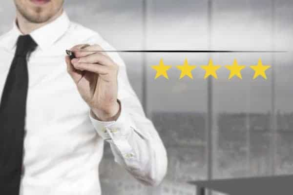 businessman in office writing five golden stars premium